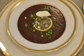 Black bean soup garnished with lemon, scallions and a dollop of creme fraiche.